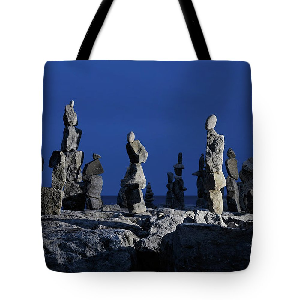 Inukshuk Tote Bag featuring the photograph Human Figures Made From Stones At Night by Oleksiy Maksymenko