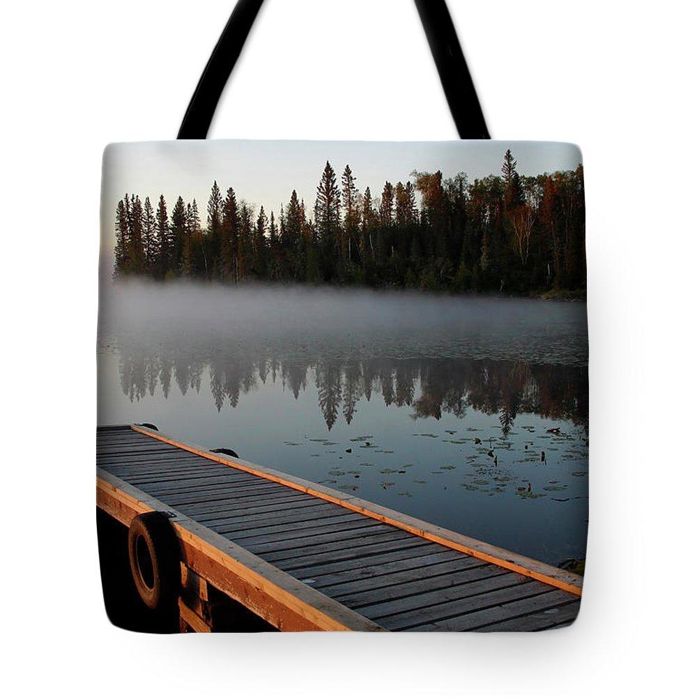 Mist Tote Bag featuring the digital art Morning Mist Over Lynx Lake In Northern Saskatchewan by Mark Duffy