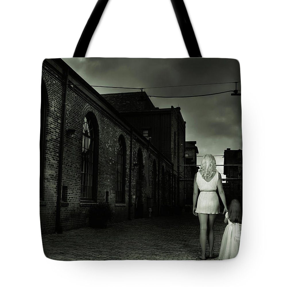Woman Tote Bag featuring the photograph Woman Walking Away With A Child by Oleksiy Maksymenko