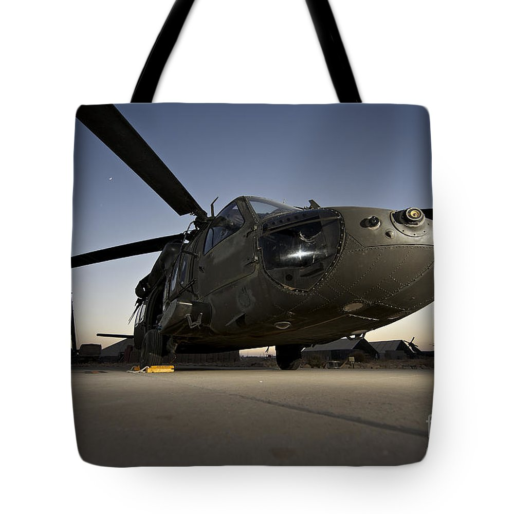 Isaf Tote Bag featuring the photograph A Uh-60l Blackhawk Parked On Its Pad by Terry Moore