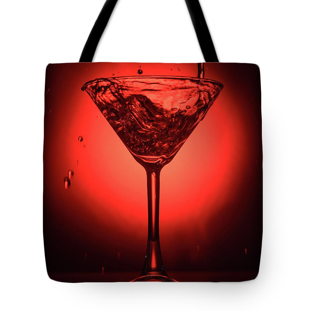 Alcohol Tote Bag featuring the photograph Cocktail Glass With Splashes On Red Background by Oleg Yermolov