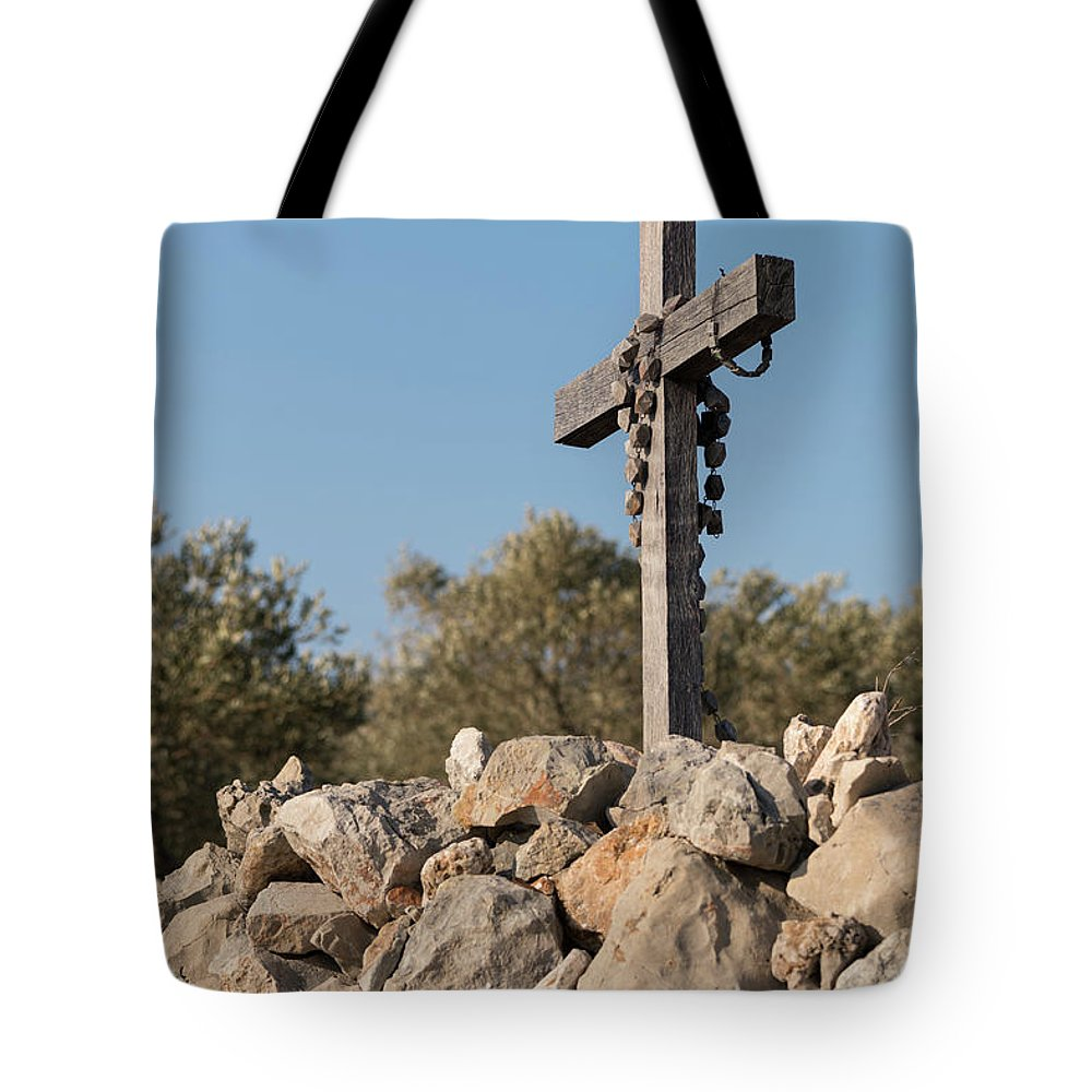 Religion Tote Bag featuring the photograph Rosary Hanging On A Small Wooden Cross On A Stone Wall by Stefan Rotter
