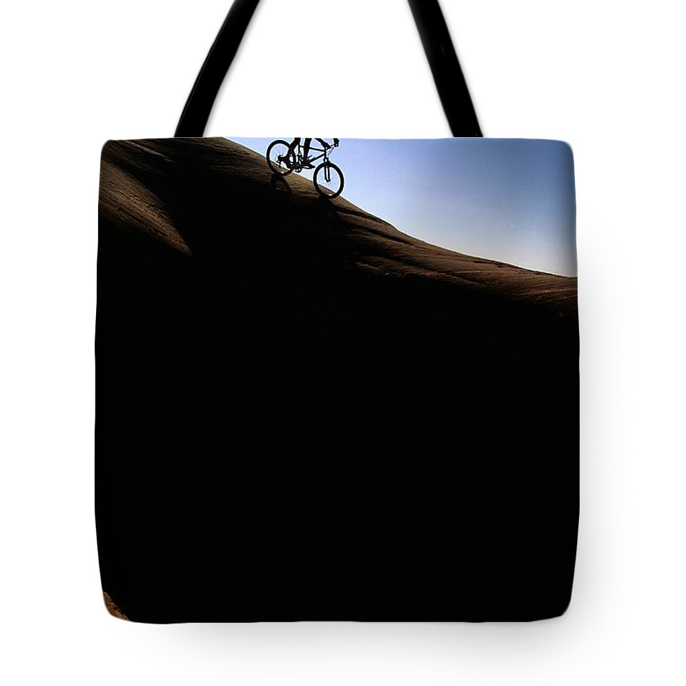 North America Tote Bag featuring the photograph A Cyclist Riding On The Slick Rock by Bill Hatcher