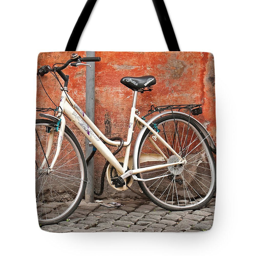 Bicycle Tote Bag featuring the photograph A Dejected Bicycle Waits Patiently On A Cobbled Street In Rome. by Lionel Everett