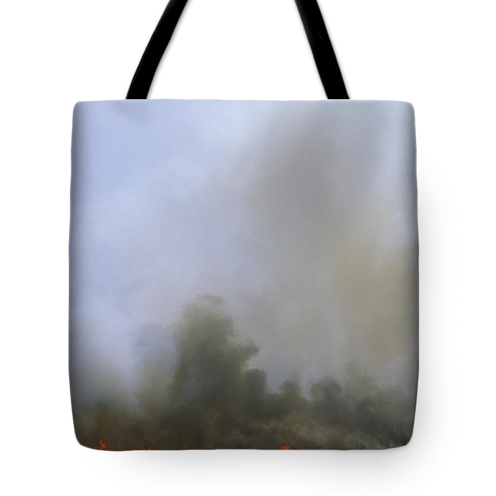 Fire Tote Bag featuring the photograph A Fire Burns In The Marsh On Ocracoke by Stephen Alvarez