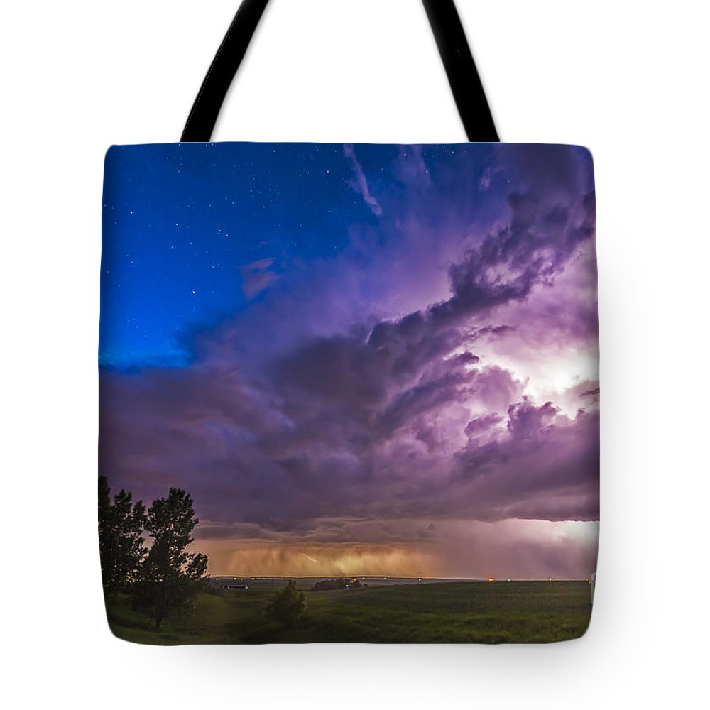 Storm Tote Bag featuring the photograph A Massive Thunderstorm Lit Internally by Alan Dyer