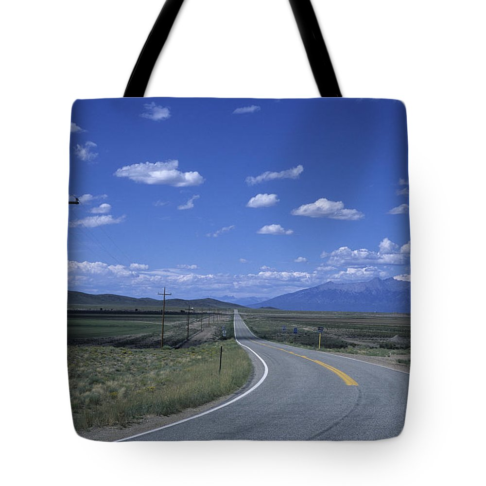 Colorado Tote Bag featuring the photograph A Road Disappears Into The Distance by Taylor S. Kennedy