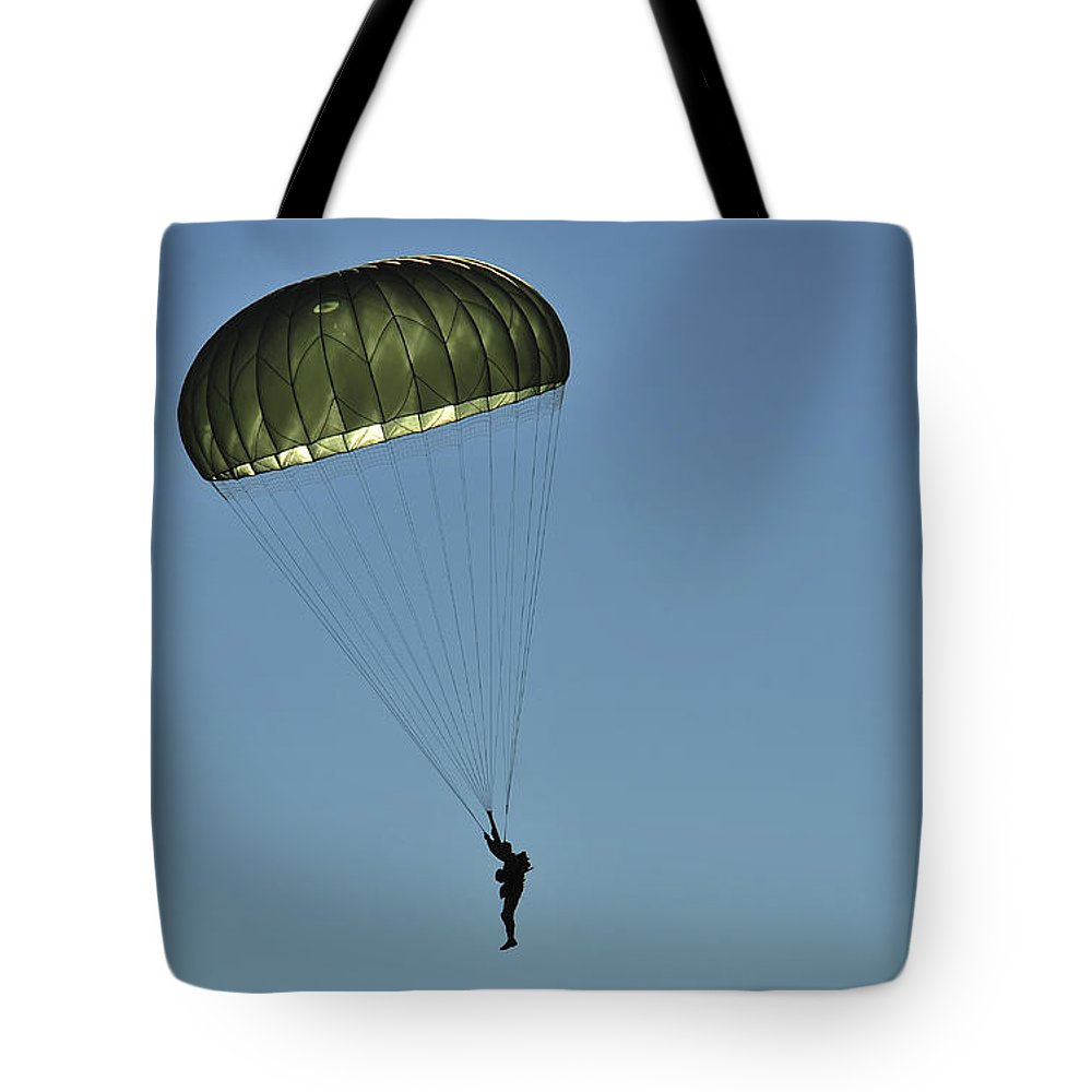 Us Air Force Tote Bag featuring the photograph A U.s. Army Paratrooper Participates by Stocktrek Images
