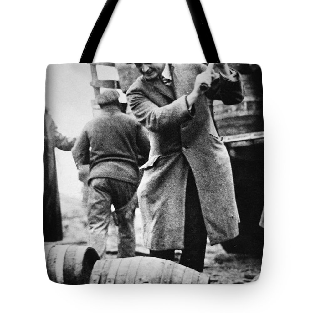 Prohibition Tote Bag featuring the photograph A Us Federal Agent Broaching A Beer Barrel From An Illegal Cargo During The American Prohibition Era by American School