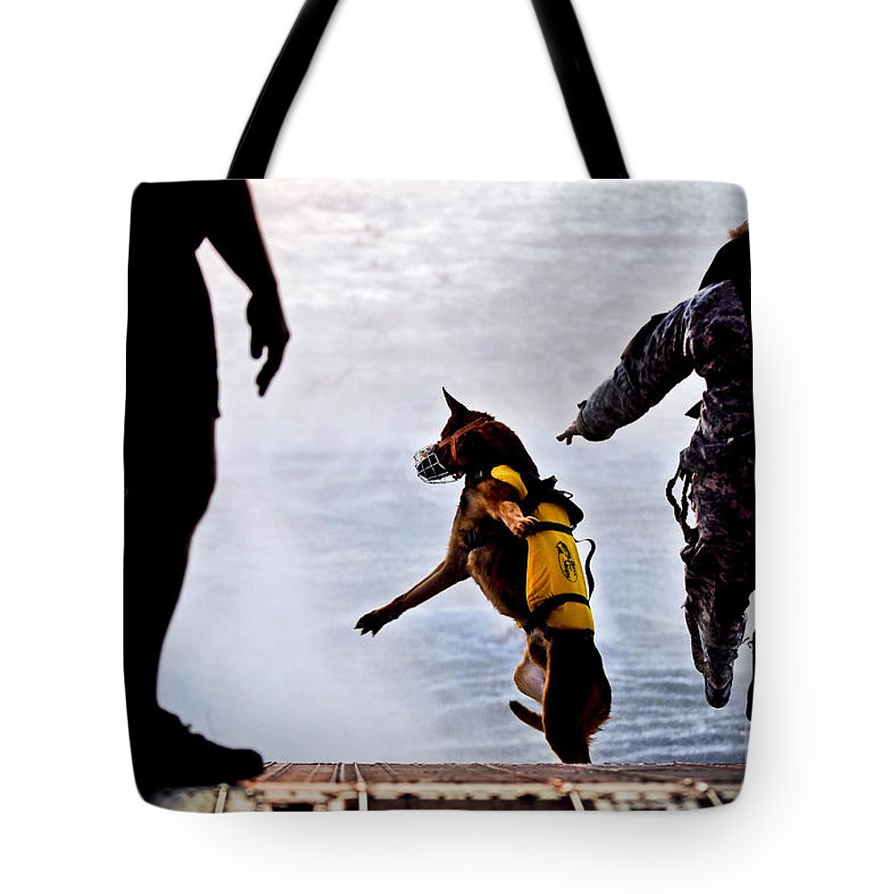 Military Tote Bag featuring the photograph A U.s. Soldier And His Military Working by Stocktrek Images