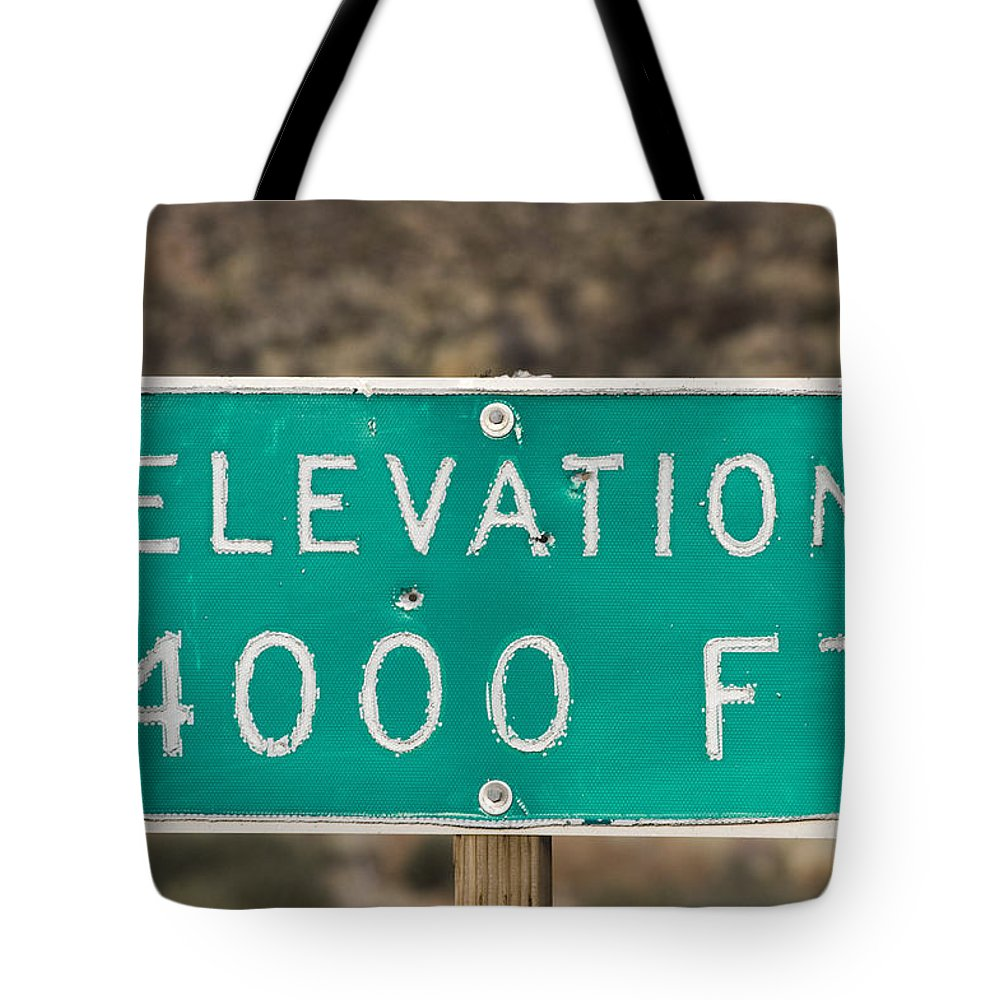 Closeups Tote Bag featuring the photograph A Weathered Elevation Sign On Highway by Rich Reid