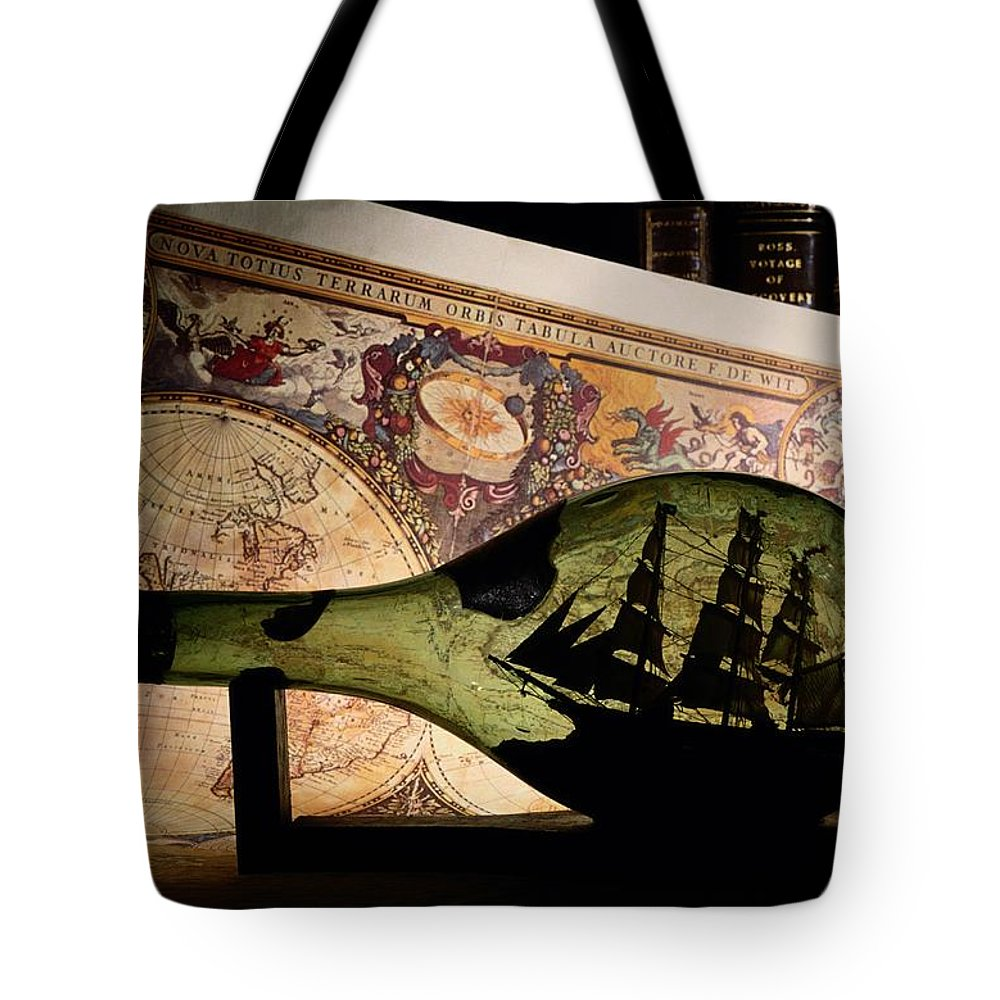 Studio Shot Tote Bag featuring the photograph An Antique Map Provides The Backdrop by Todd Gipstein