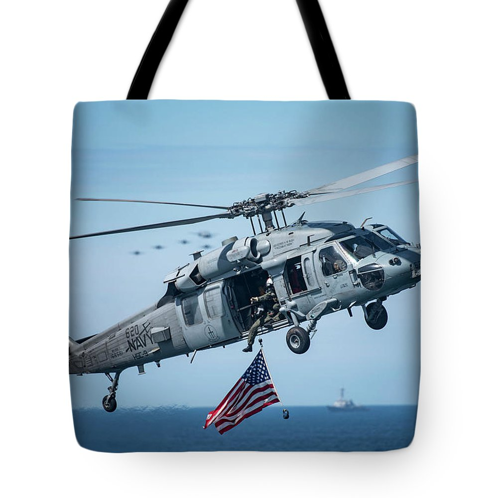 Military Tote Bag featuring the painting An Mh-60s Sea Hawk Helicopter Displays The American Flag. by Celestial Images