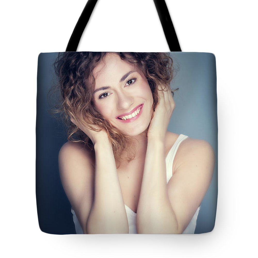 Girl Tote Bag featuring the photograph Attractive Young Woman Touching Her Hair And Face. by Michal Bednarek