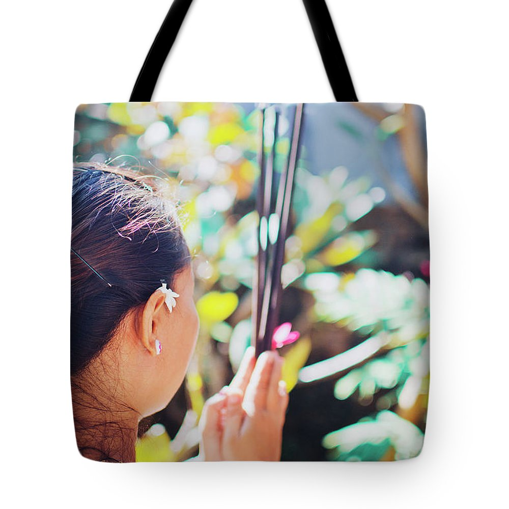 30's Tote Bag featuring the photograph Beautiful Asian Woman Holding Incense Sticks During Hindu Ceremony In Bali, Indonesia by Srdjan Kirtic