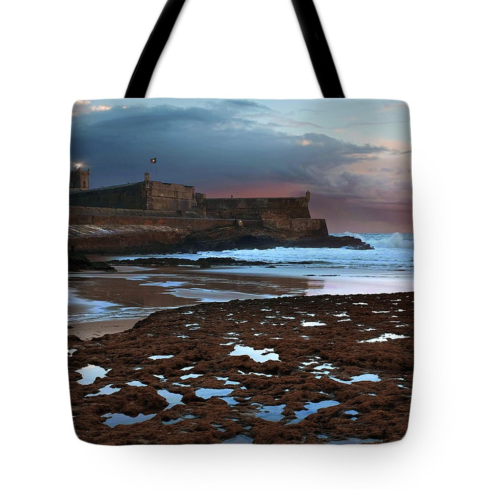 Sunset Tote Bag featuring the photograph Fort In Carcavelos Beach by Carlos Caetano