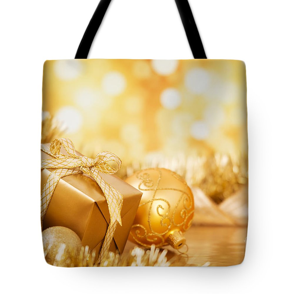 Baubles Tote Bag featuring the photograph Christmas Scene With Gold Baubles And Gift On A Gold Background by Sara Winter