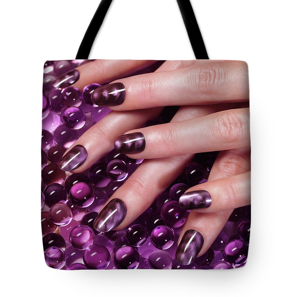 Manicure Tote Bag featuring the photograph Closeup Of Woman Hands With Purple Nail Polish by Maxim Images Prints