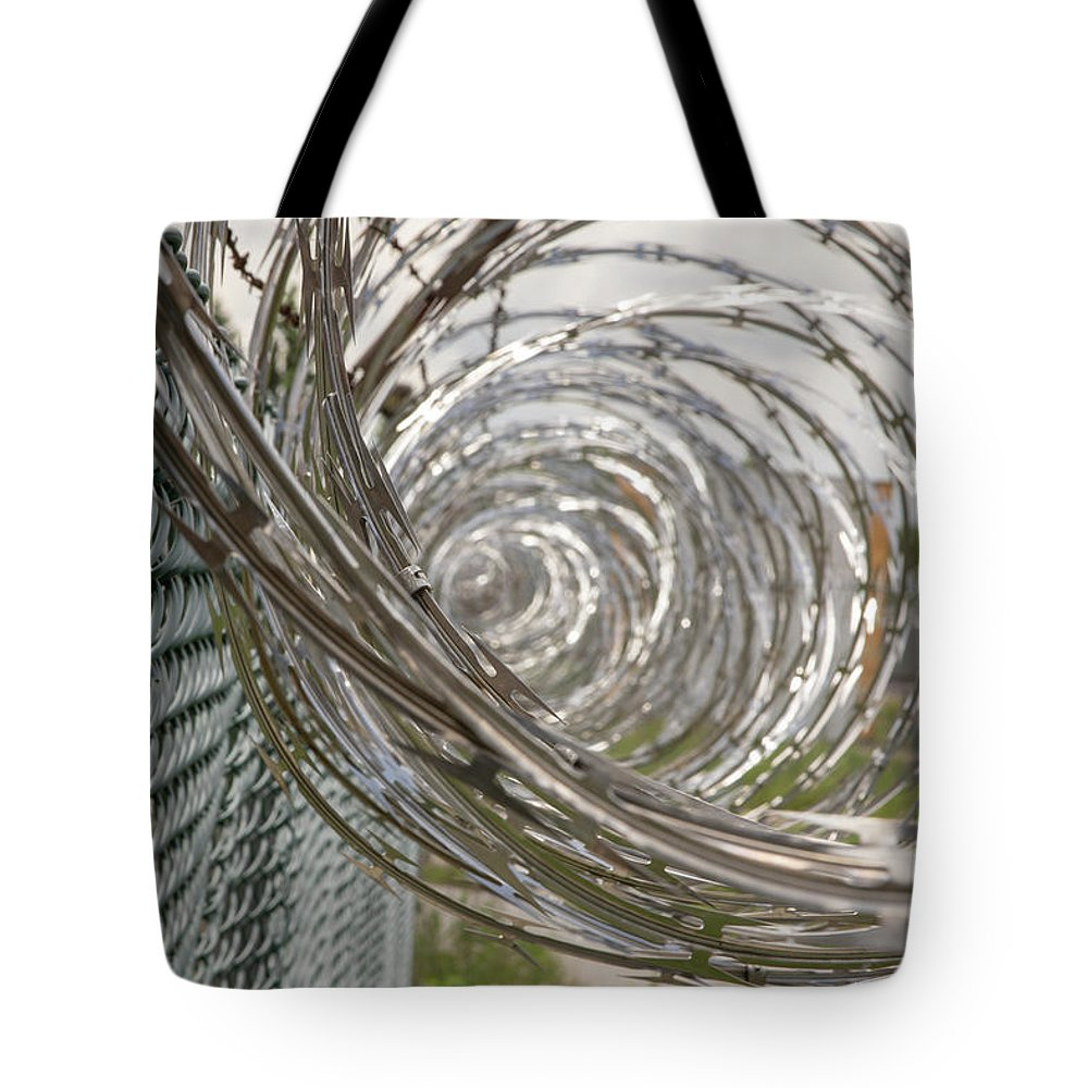 Abandoned Tote Bag featuring the photograph Coiled Razor Wire On Fence by Karen Foley