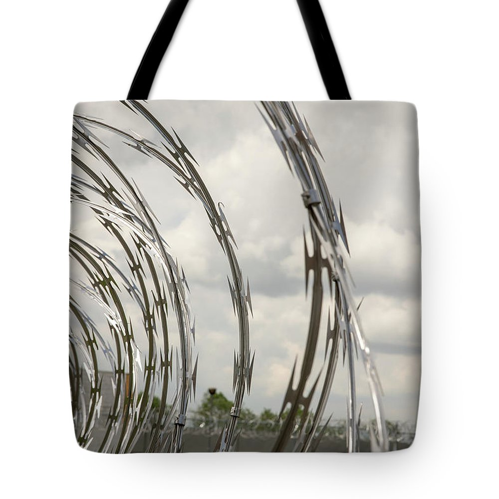 Abandoned Tote Bag featuring the photograph Coils Of Razor Wire On Fence by Karen Foley