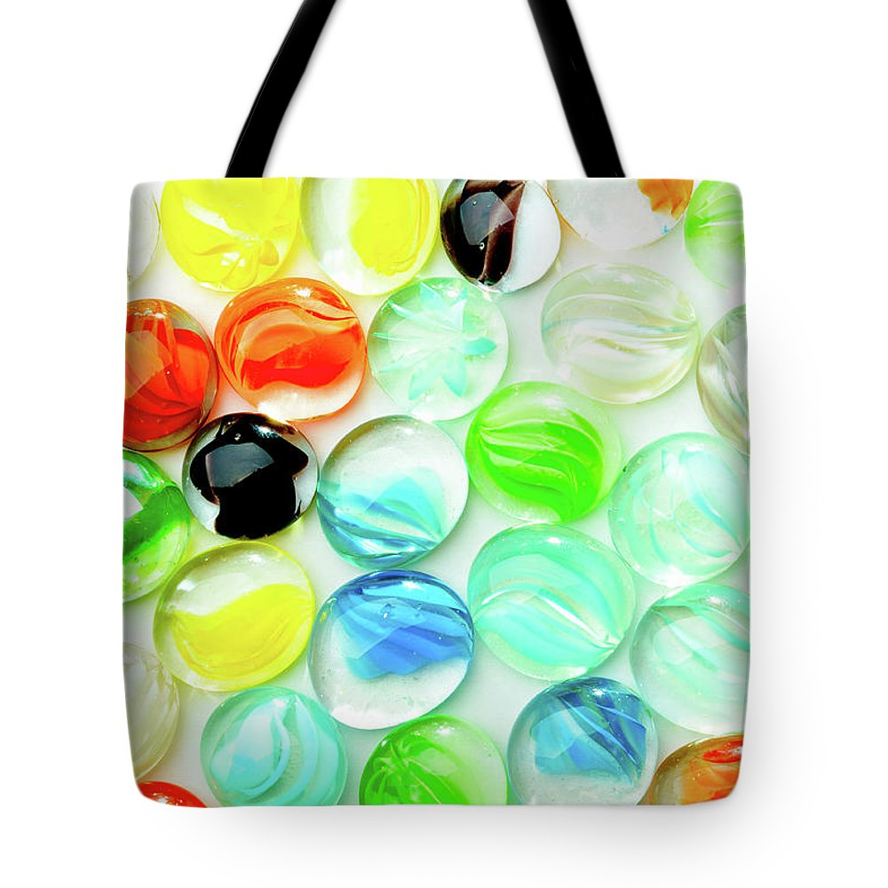 Abstract Tote Bag featuring the photograph Colored Glass Beads On White Background by Alain De Maximy