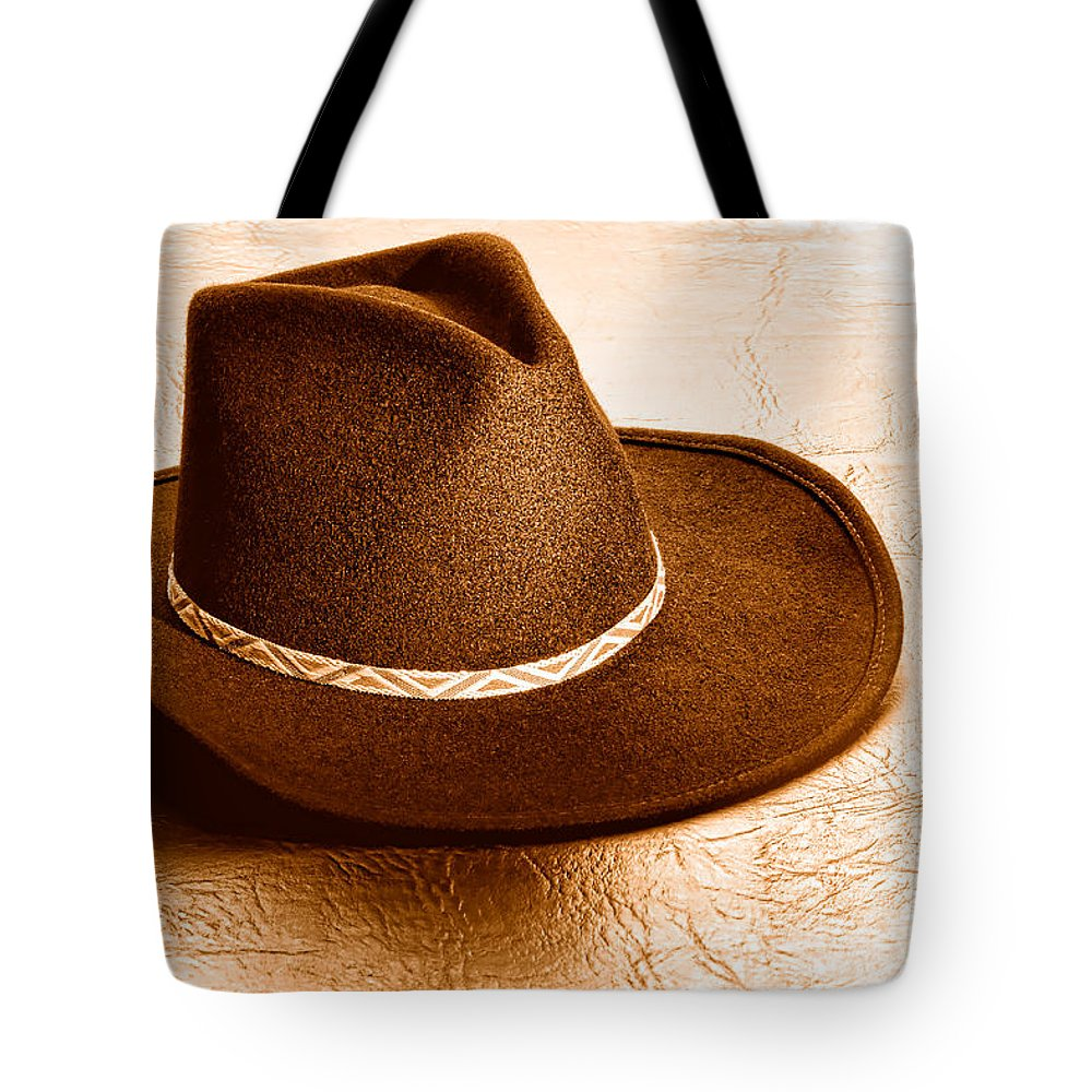 Cowboy Tote Bag featuring the photograph Cowboy Hat On Leather - Sepia by Olivier Le Queinec