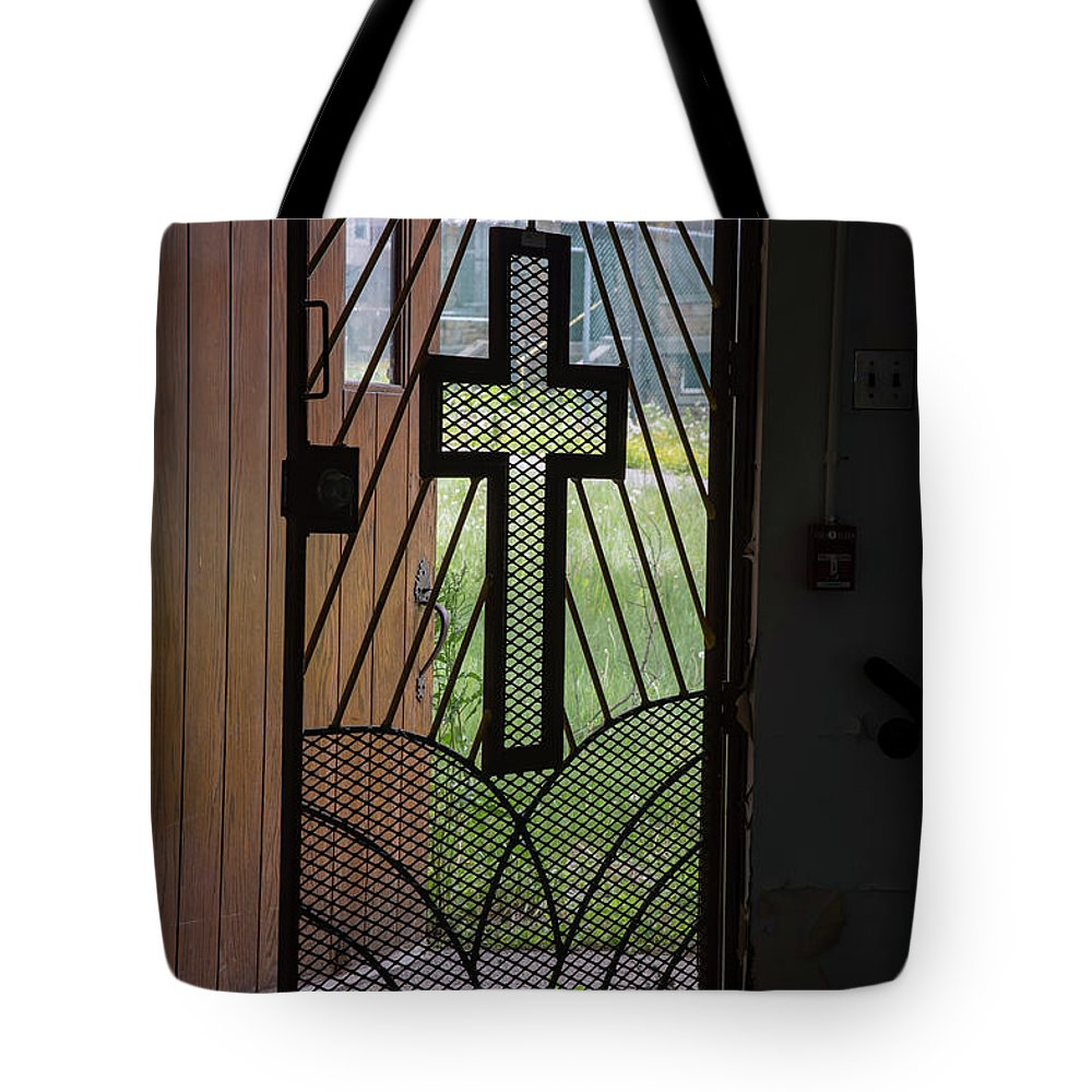 Abandoned Tote Bag featuring the photograph Cross On Church Door Open To Prison Yard Fence With Razor Wire by Karen Foley