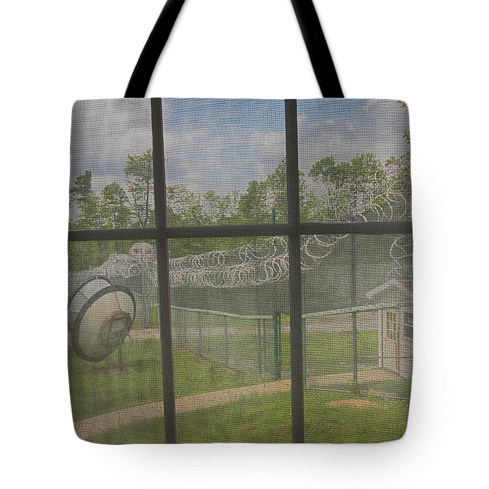 Abandoned Tote Bag featuring the photograph Prison Yard With Razor Wire, Guard House And Satellite Dish by Karen Foley