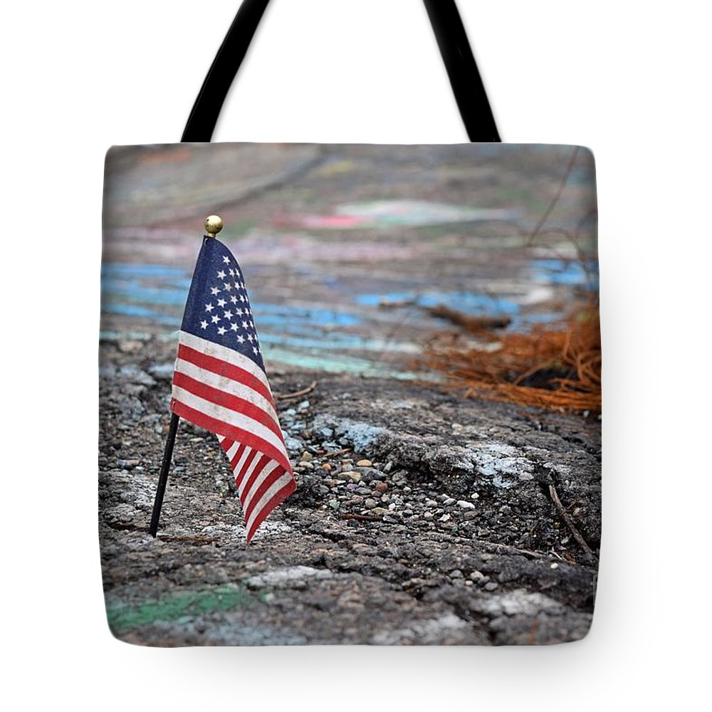 May Tote Bag featuring the photograph Flag In A Crack In The Pavement by Ben Schumin