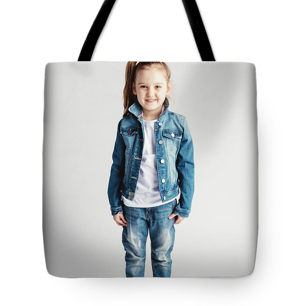 Girl Tote Bag featuring the photograph Girl In Jeans Clothes On White Background. by Michal Bednarek