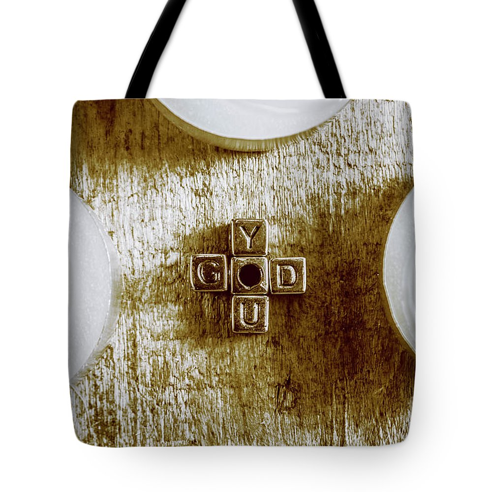 God Tote Bag featuring the photograph God Is You Metal Lettering Typography Near White Candles, Faith by Jorgo Photography - Wall Art Gallery