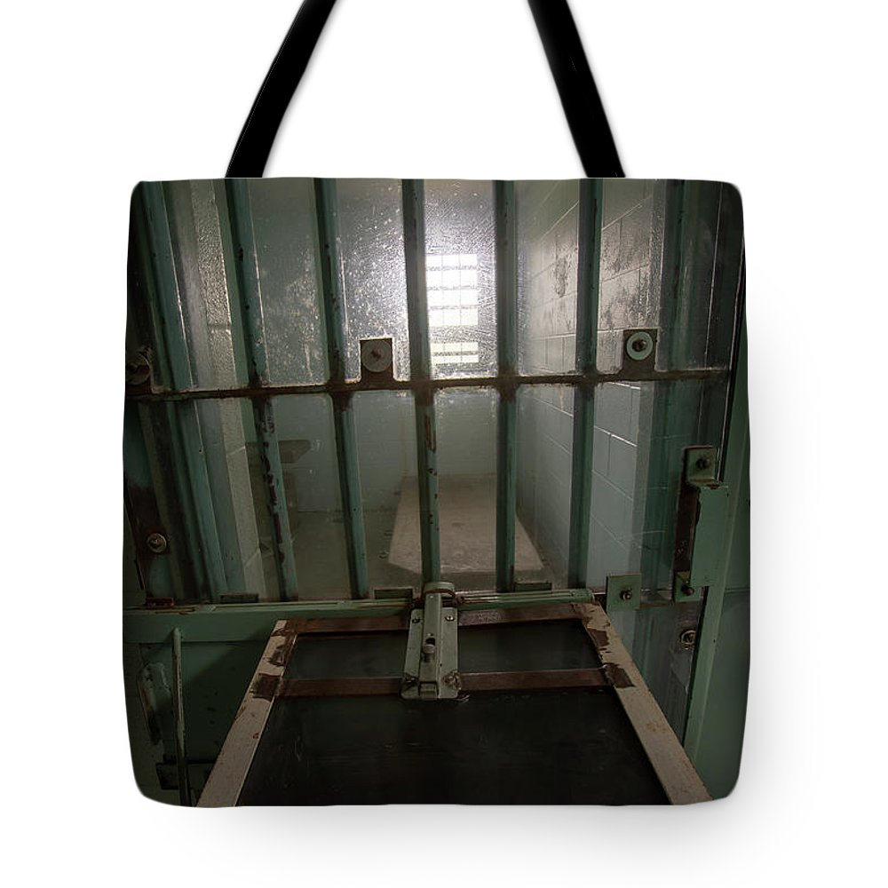 Abandoned Tote Bag featuring the photograph High Risk Solitary Confinement Cell In Prison Through Bars by Karen Foley