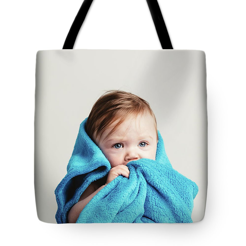 Baby Tote Bag featuring the photograph Little Baby Girl Tucked In A Cozy Blue Blanket. by Michal Bednarek