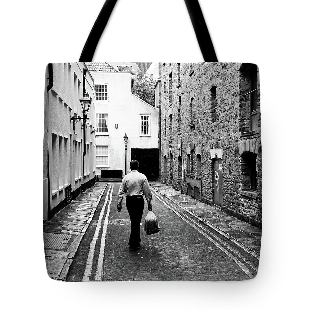 Architecture Tote Bag featuring the photograph Man Walking With Shopping Bag Down Narrow English Street by Jacek Wojnarowski