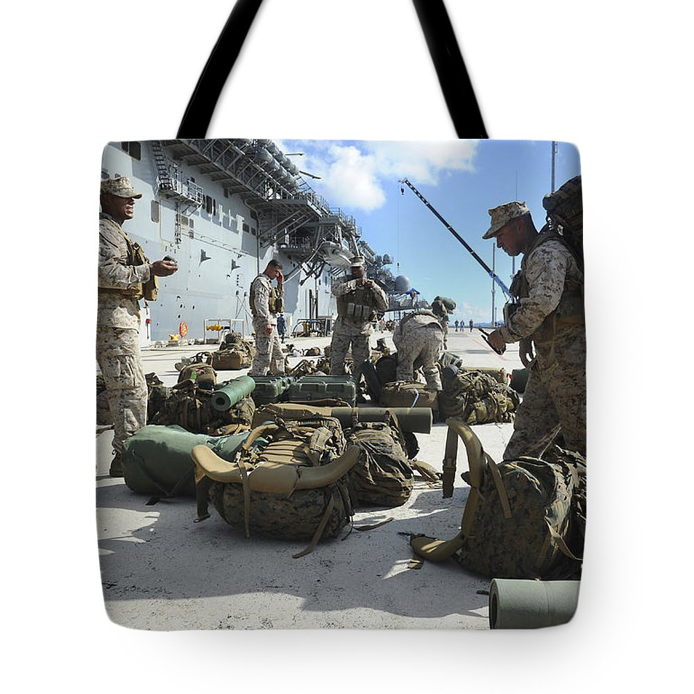 Uss Bonhomme Richard Tote Bag featuring the photograph Marines Move Gear During An Embarkation by Stocktrek Images