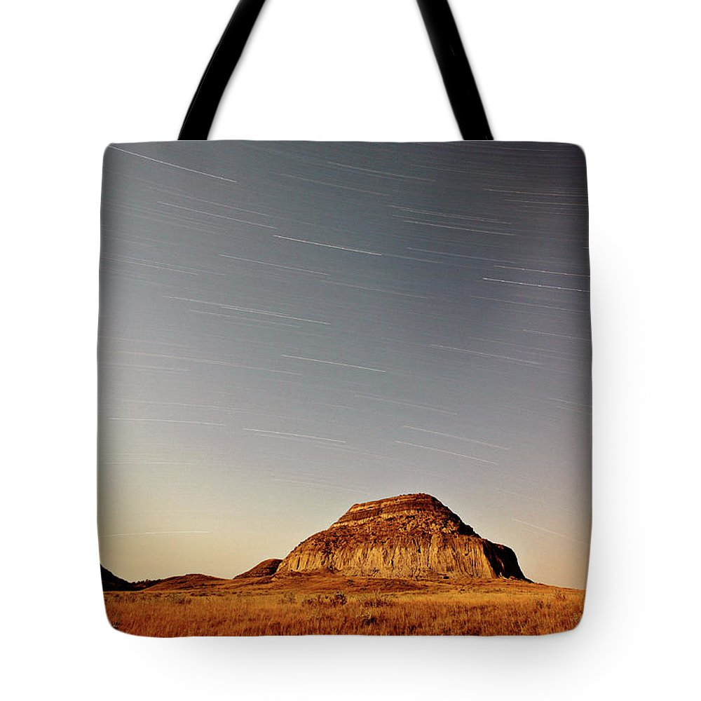 Castle Butte Tote Bag featuring the digital art Moon Lit Castle Butte And Star Tracks In Scenic Saskatchewan by Mark Duffy