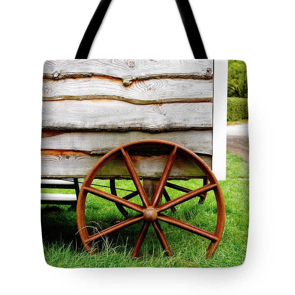 Aged Tote Bag featuring the photograph Old Cart Wheel by Tom Gowanlock