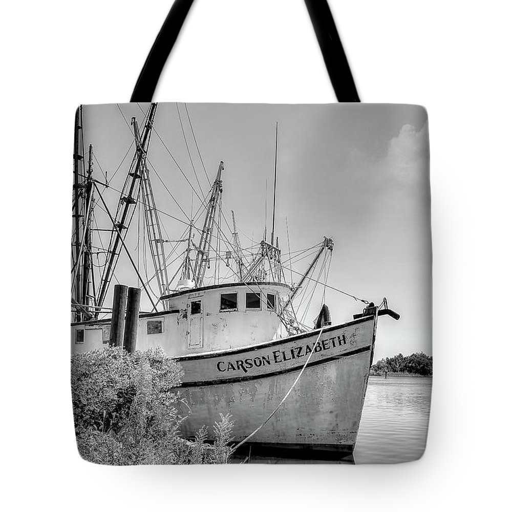 Shrimp boats tote bag featuring the photograph old shrimp boat black and white by kathy baccari