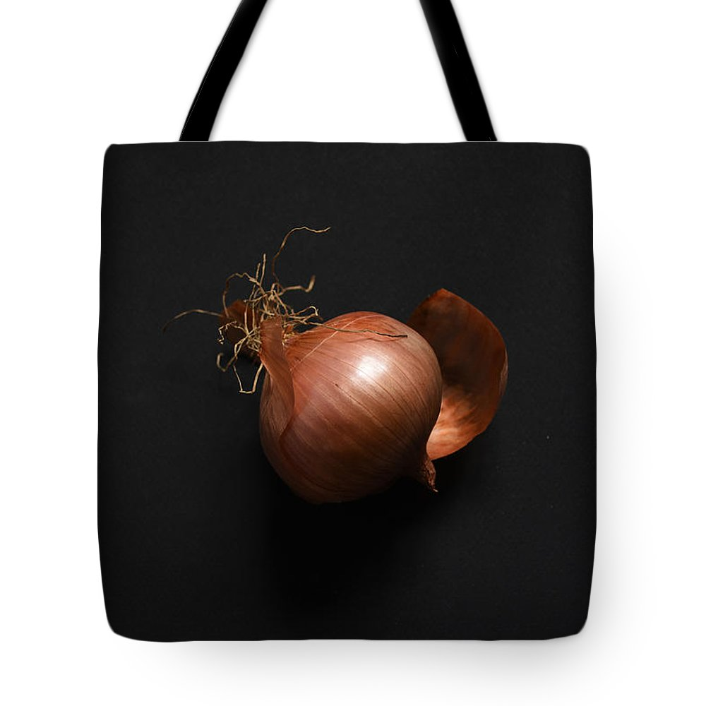 Onion Tote Bag featuring the photograph One Onion On A Black Background by Ludmila SHUMILOVA