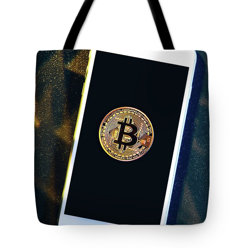 Money Tote Bag featuring the photograph Phone With A Bitcoin Laying On Top Of It. by Michal Bednarek