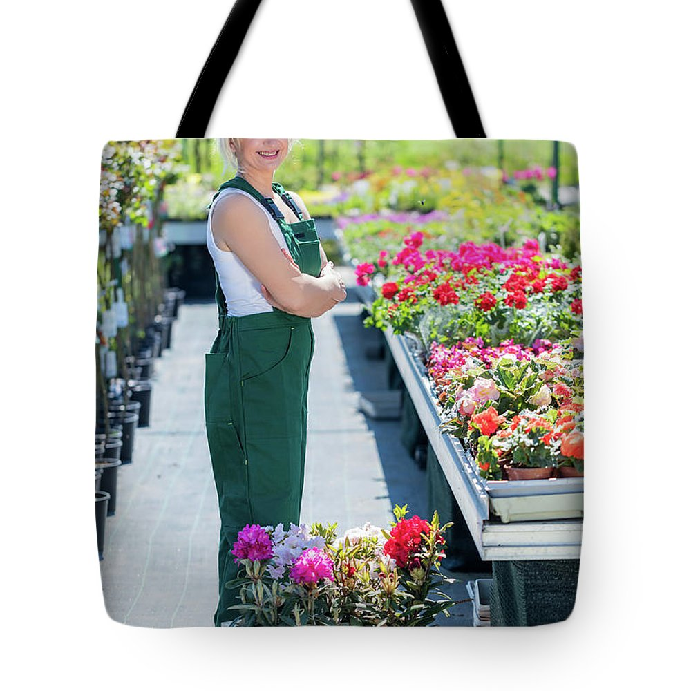 Garden Tote Bag featuring the photograph Professional Gardener At Work In A Nursery. by Michal Bednarek