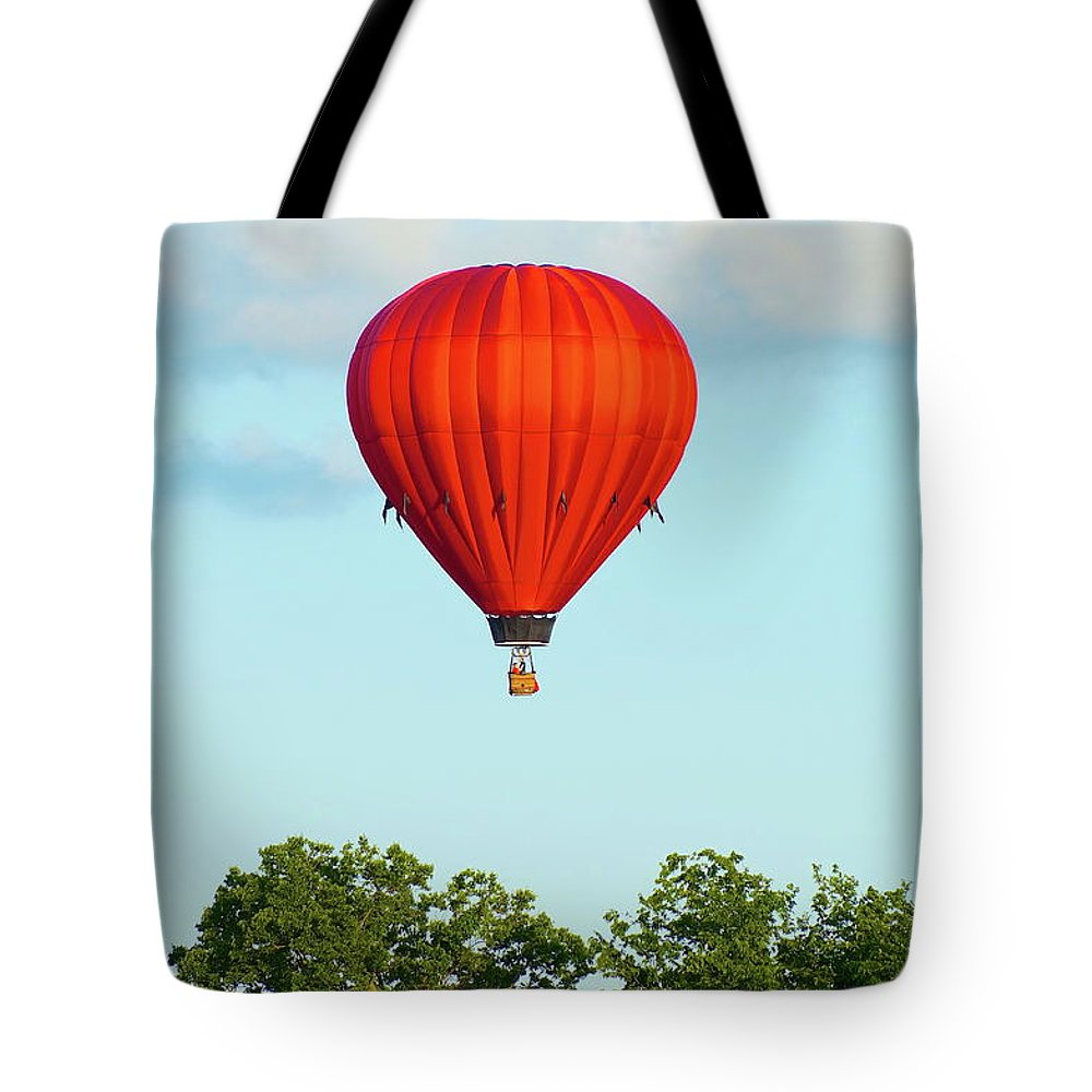 Balloons Tote Bag featuring the photograph Red Above The Trees by Linda Cupps