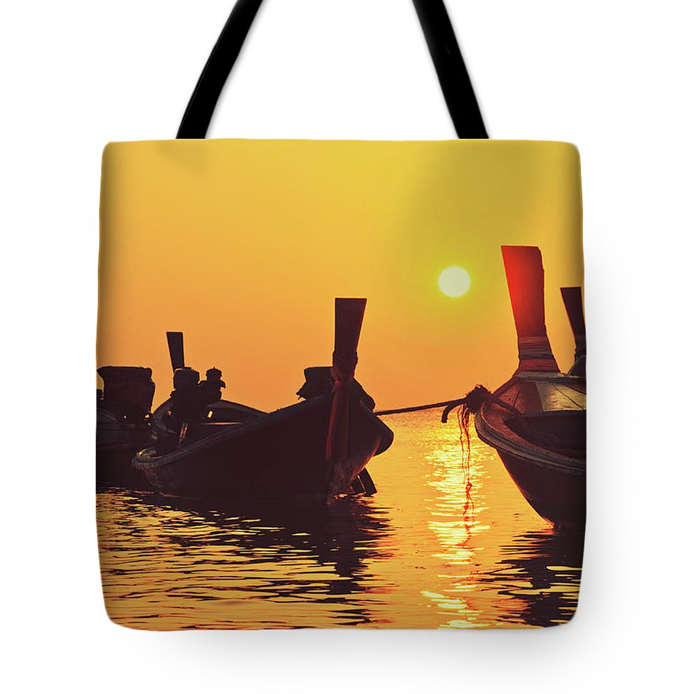 Background Tote Bag featuring the photograph Six Thai Wooden Boats Floating And Glittering In The Lagoon During Golden Sunset Koh by Srdjan Kirtic