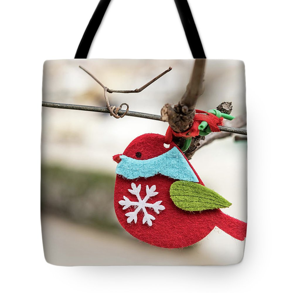 Easter Tote Bag featuring the photograph Small Red Handicraft Bird Hanging On A Wire by Stefan Rotter
