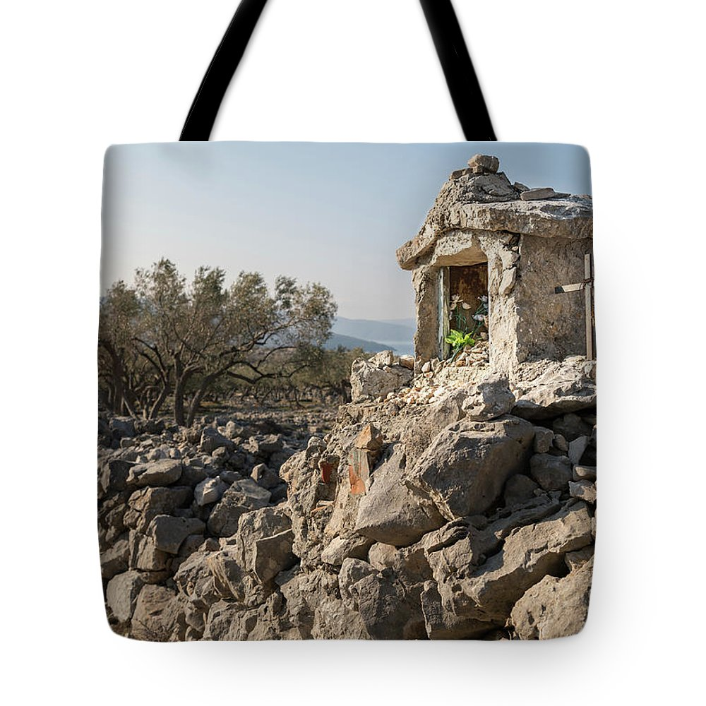 Religion Tote Bag featuring the photograph Small White Chapel And A Metal Cross On A Stone Wall Near Cres by Stefan Rotter