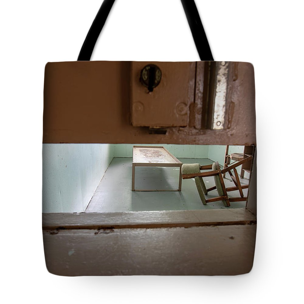 Abandoned Tote Bag featuring the photograph Solitary Confinement Cell Through Door Slat by Karen Foley