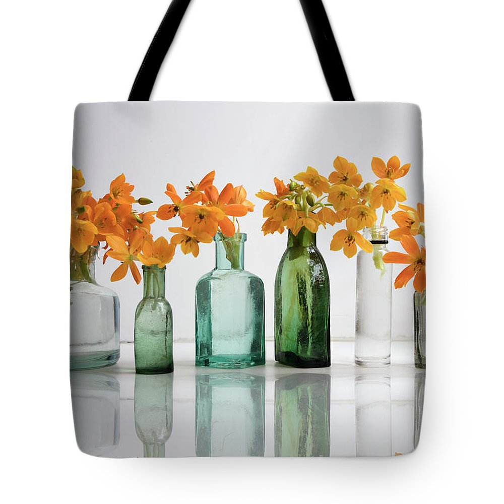 Background Tote Bag featuring the photograph the Blooming yellow Ornithogalum Dubium in a transparent bottle instead vase by Elena Rostunova