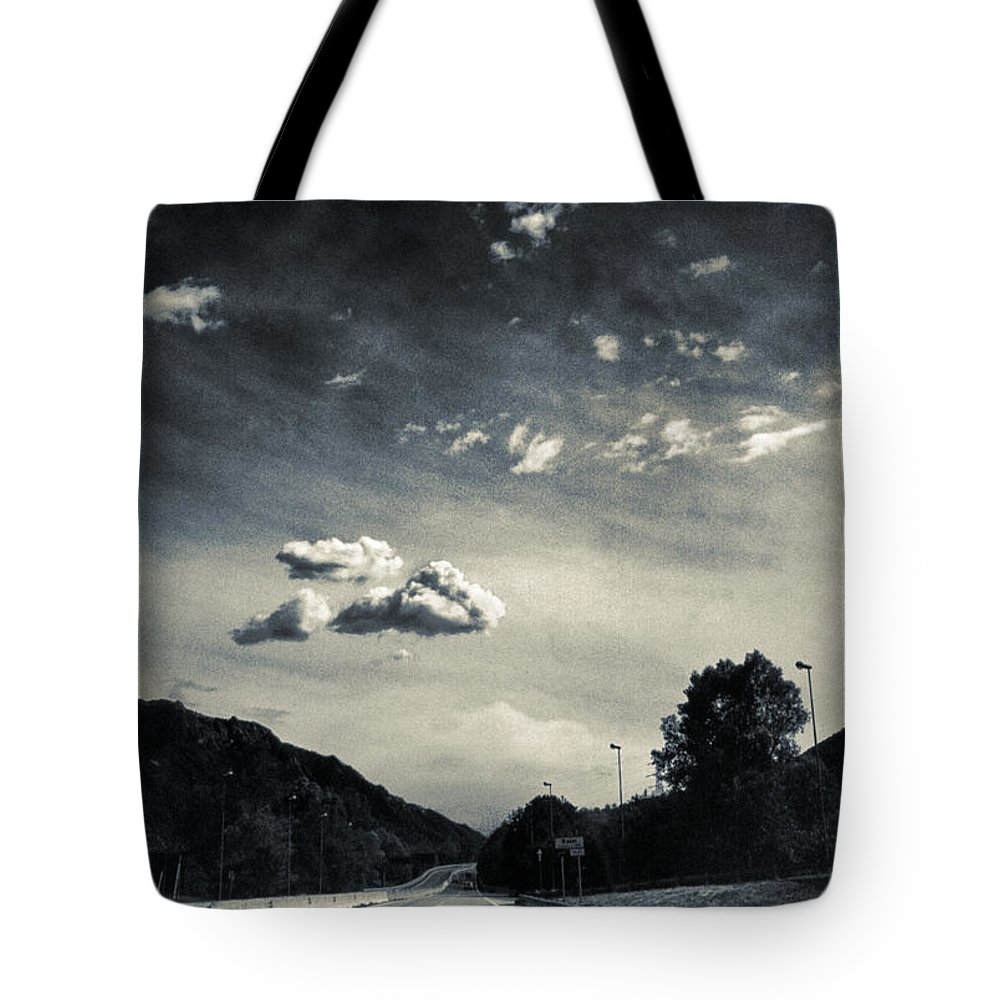 Road Tote Bag featuring the photograph The Road And The Clouds by Silvia Ganora