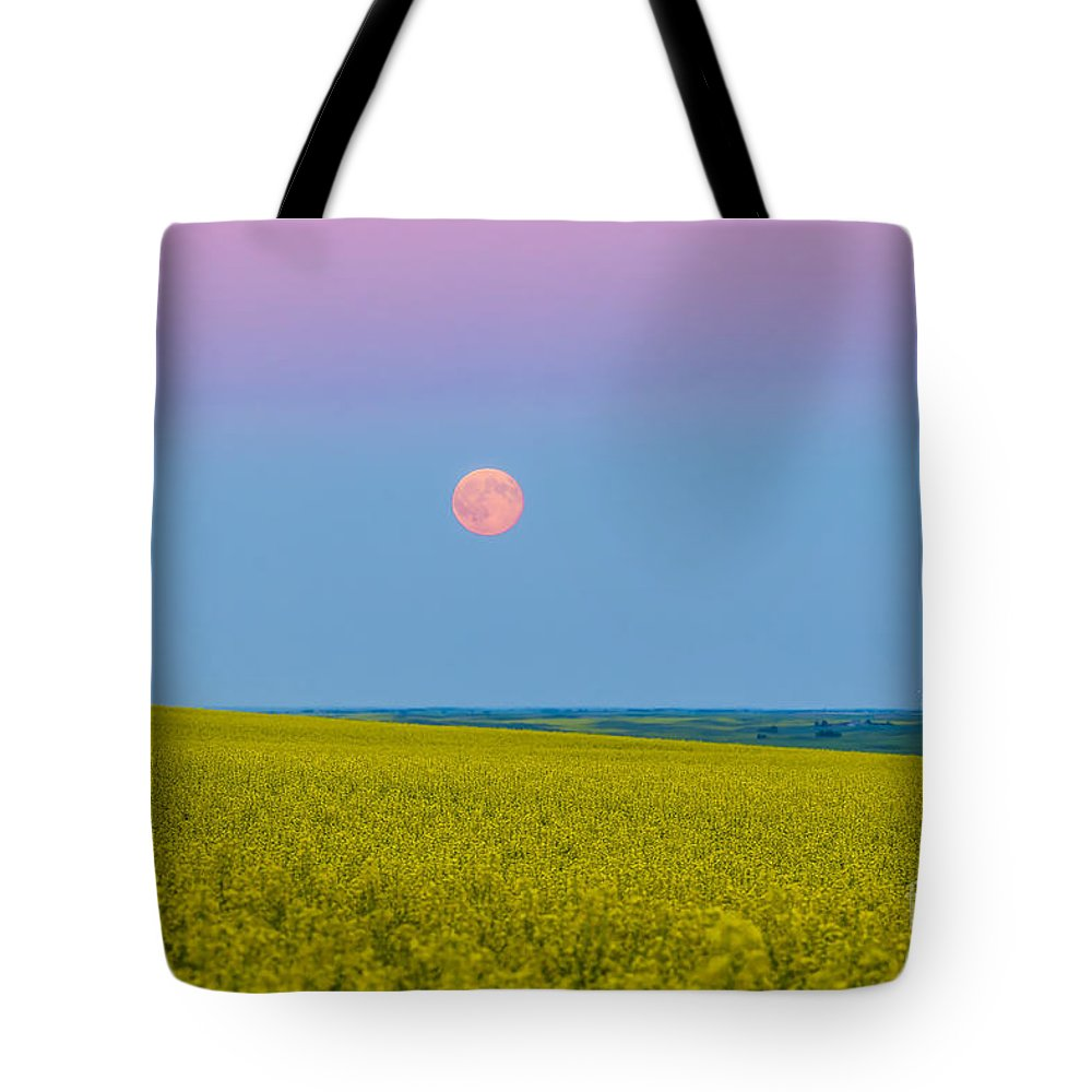 Alberta Tote Bag featuring the photograph The Supermoon Rising Above A Canola by Alan Dyer