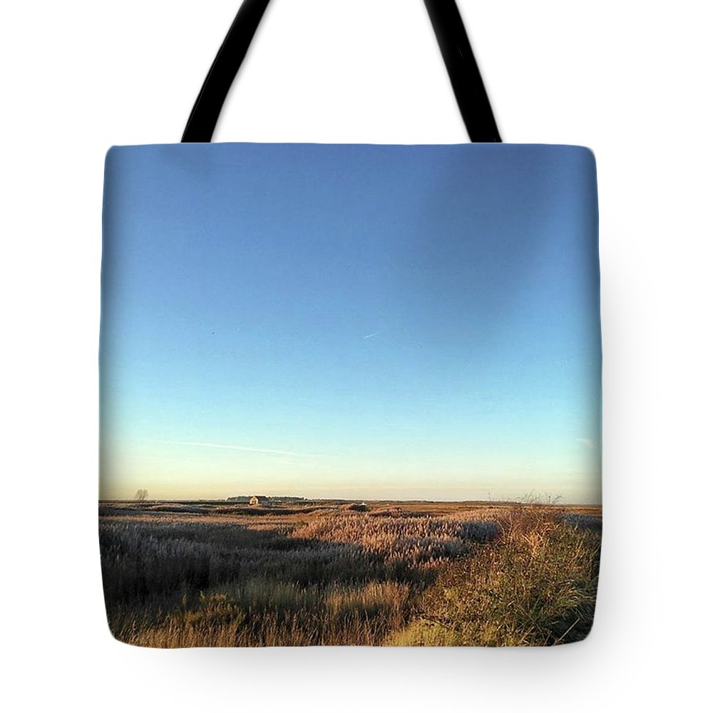 Natureonly Tote Bag featuring the photograph Thornham Marsh Lit By The Setting Sun by John Edwards